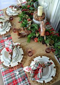 03 a lush evergreen garland with pinecones apples deer figurines and a candle lantern with nuts