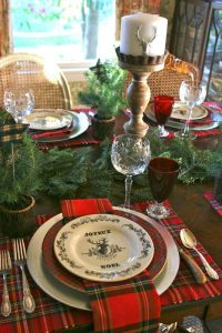 04 plaid mats and plates an evergreen garland deer candles red glasses for a traditional feel