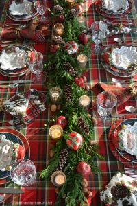 05 a plaid tablecloth a greenery table runner with pinecones apples plaid ornaments and mercury glass candle holders