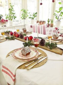 10 a cozy rustic tablescape with gingerbread house cookies evergreens pinecones apples and candles