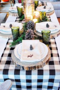 13 large pinecones green glasses greenery and mercury glass candle holders wood slices as chargers