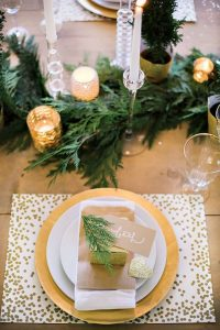 17 a modern glam tablescape with a gold sequin placemat evergreens gold mercury glass candle holders and glitter touches