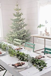 18 a modern table setting with a foliage garland and large gingerbread men cookies for a cool look