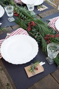 20 a modern tablescape with an evergreen and berry garland and striped napkins