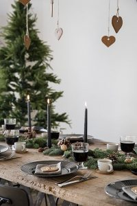 21 an evergreen garland with pinecones and nuts black candles and gingerbread cookies hanging from above